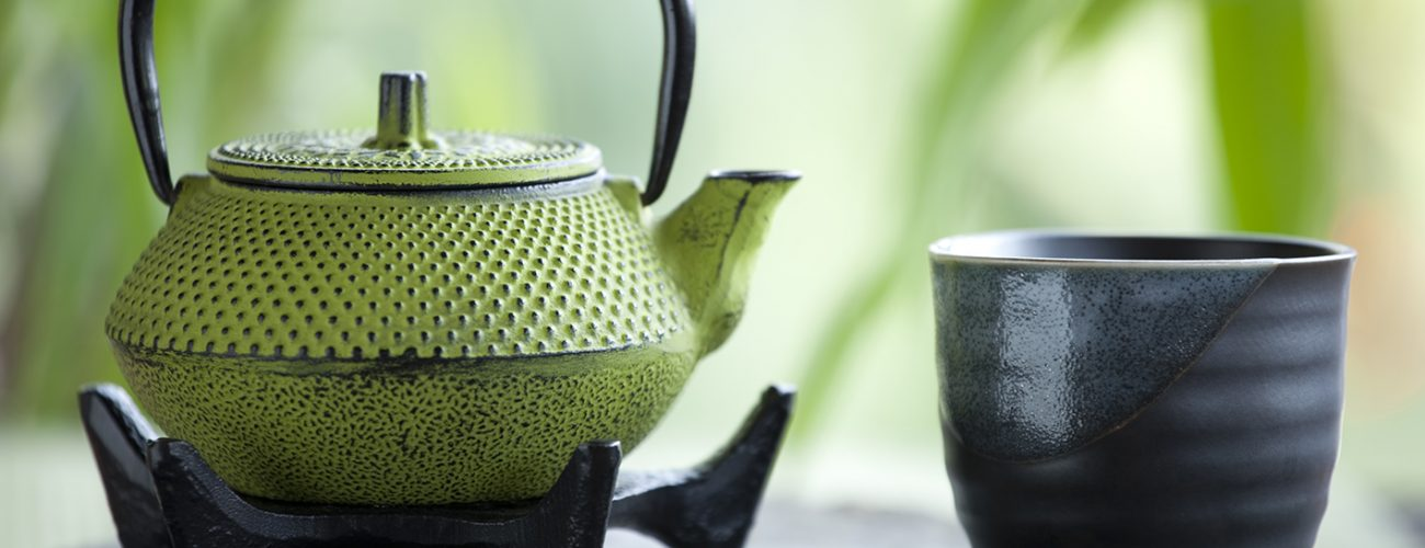 Green tea and cast iron teapot with bamboo background.  You may also like: